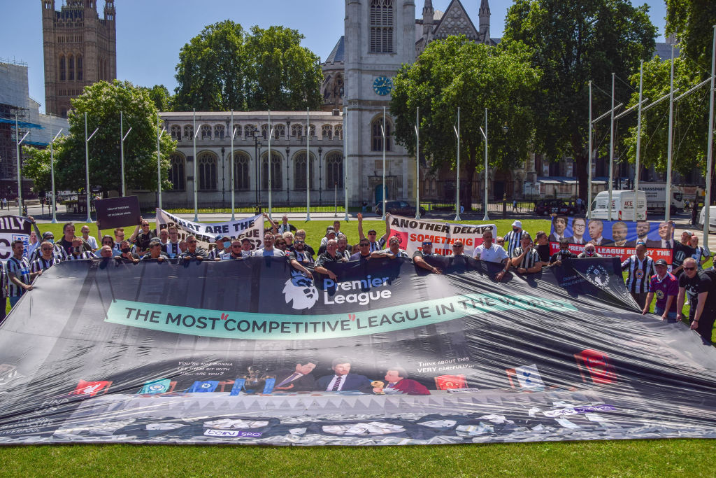 Protesters hold a large Premier League banner during the